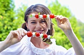 Young woman with tomato and mozzarella skewers