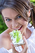 Young woman eating crispbread with cottage cheese & cucumber