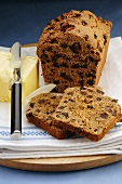 Fruit loaf, partly sliced, with butter
