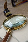 Magnifying glass, writing paper and bottle of ink