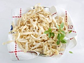 Home-made pasta on tea towel in bowl
