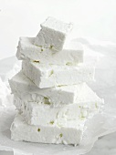Pieces of feta cheese stacked on paper