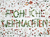 'Fröhliche Weihnachten' (Merry Christmas in German) written in berries & foliage