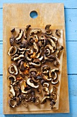 Dried mushrooms on chopping board (overhead view)