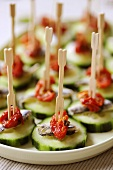 Appetisers: cucumber slices with dried tomatoes and anchovies