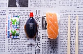 Nigiri sushi, soy sauce, wasabi and chopsticks on newspaper