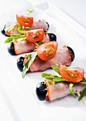 Ham rolls with olives, rocket and tomatoes