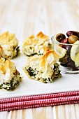 Pieces of spinach and feta pie with filo pastry, olives