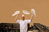Italian pizza baker throwing dough into the air