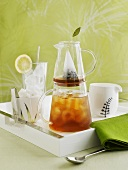 Iced tea in jug, ice cubes and ice tongs