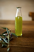 A small bottle of olive oil and an olive sprig