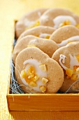 Almond macaroons with icing and orange peel in wooden box