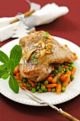 Piece of turkey leg on carrots and peas (Christmas)