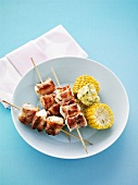 Bacon-wrapped chicken skewers with corn on the cob and herb butter