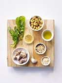 Ingredients for pasta and tuna dish on chopping board (overhead view)