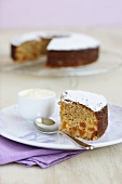 Piece of apricot orange cake with icing sugar in front of rest of cake