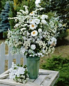 Vase of white flowers out of doors