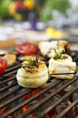 Eel rolls with rosemary and tomato halves on barbecue