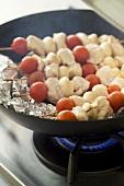 Making smoked turkey, tomato and mushroom kebabs
