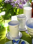 Tisch mit Kaffeebechern und lila Flieder