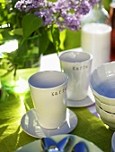 Coffee mugs and purple lilac on table