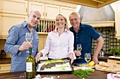 Friends with fish and white wine in kitchen