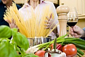 Woman putting spaghetti into pan, herbs & vegetables in front