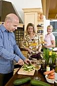 Zwei Frauen und ein Mann mit Gemüse in der Küche
