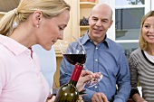 Woman smelling bouquet of red wine, couple watching with interest