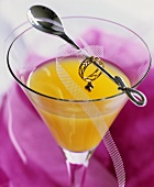 Drink made with orange juice, cocktail spoon with ring & net ribbon