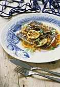 Fried fish with orange slices and pine nuts