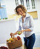Young woman holding a basket of fresh fruit