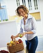 Junge Frau hält Korb mit frischem Obst