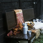 Autumn leaves, milk can, cup, sea buckthorn & throws on bench