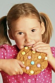 Girl eating a giant biscuit decorated with chocolate beans
