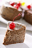 A piece of chocolate cheesecake with a candied cherry