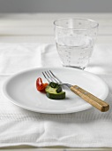 Courgette and pepper on white plate, glass of water