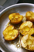 Frying apple halves in a frying pan