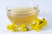 A cup of St. John's wort tea and St. Johns' wort flowers