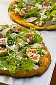 Pizza topped with foie gras, rocket and figs
