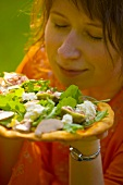 Young woman smelling pizza topped with foie gras, rocket & figs