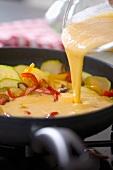 Fritatta zubereiten: Eiermasse in die Pfanne gießen