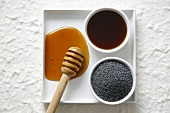 Honey with honey dipper and poppy seeds