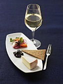 A piece of cheese with crispbread and white wine