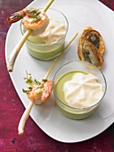 Ramsons (wild garlic) foam soup with prawns on lemon grass skewers