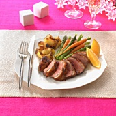 Roast duck breast with orange wedges and vegetables