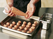 Making meatballs with a piping bag