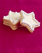 Star-shaped biscuits with dragées against purple background
