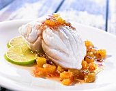 Red snapper with pineapple sauce and slices of lime