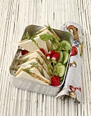 Tuna tramezzini with cucumber and radishes in metal box